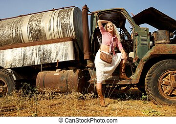 Attractive blond woman near the old car