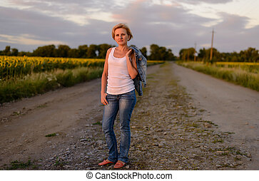 Attractive blond woman on a rural farm road