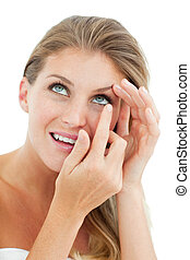 Attractive blond woman putting a contact lens isolated on a...