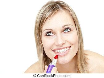 Attractive blond woman putting lipstick