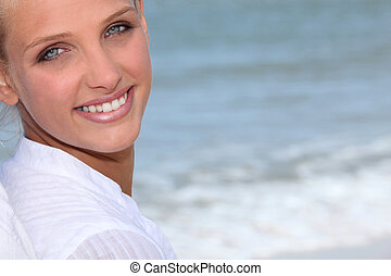 Attractive blond woman stood on the beach