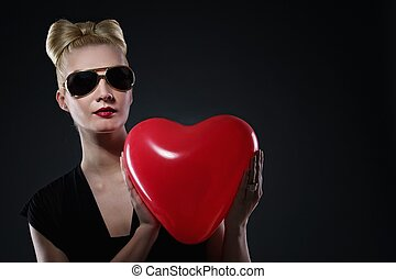 Attractive blond woman with a red balloon