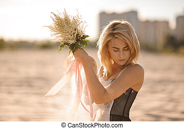 Attractive blond woman with flowers in hands