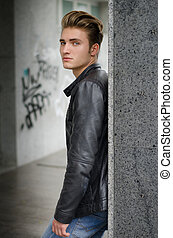 Attractive blond young man in city environment, standing ...
