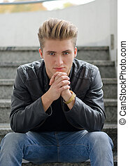 Attractive blond young man sitting on stairs