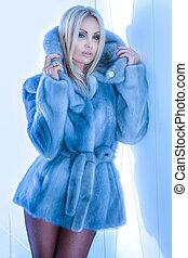 Fashionable blonde beautiful woman posing, wearing fur coat and looking at camera.