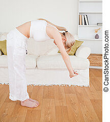 Attractive blonde female stretching in the living room