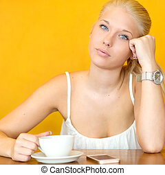 Attractive blonde girl drinking coffee at cafe