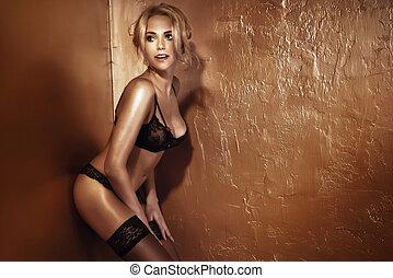 Attractive blonde girl posing in black lingerie.