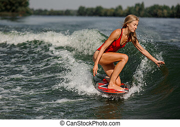 Attractive blonde girl riding on the red wakeboard