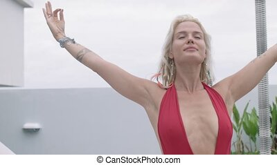 Attractive blonde hair woman in the red swimsuit practicing yoga on the open veranda of the hotel