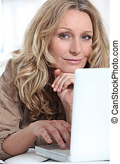 Attractive blonde haired woman using a laptop computer