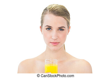 Attractive blonde holding glass of orange juice