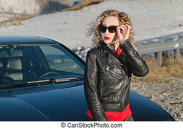 Attractive blonde in sunglasses and leather clothes stands near a black sports car on a country road in the mountains at sunset. Retro style 90s