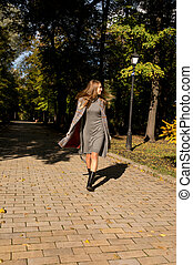 Attractive blonde model with long hair in knit dress and warm coat walking in the park in sunny day