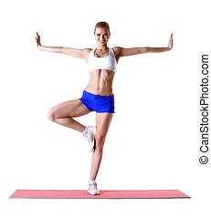 Attractive blonde posing on mat in studio