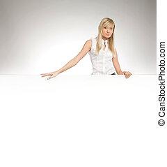 Attractive blonde secretary over white empty board, lots of copyspace