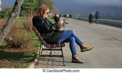 attractive blonde sitting bank and using tablet computer at outdoor