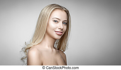 Attractive blonde smiling woman portrait on gray background