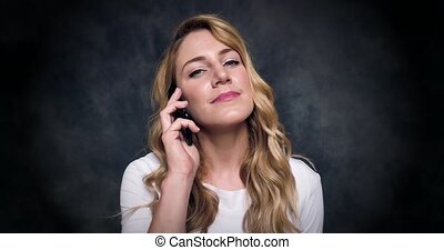 Attractive blonde speaks by a mobile phone on a dark...
