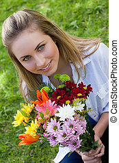 Attractive blonde teenager holding a beautiful bunch of flower