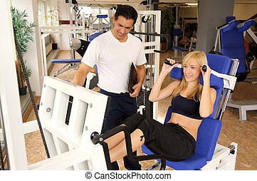 Attractive blonde woman and her trainer in a gym