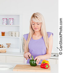 Attractive blonde woman cutting vegetables in modern kitchen interior in her appartment