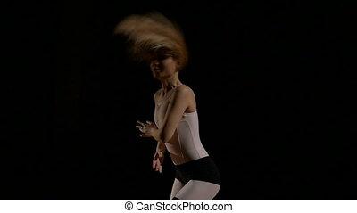 Attractive blonde woman dancing on black