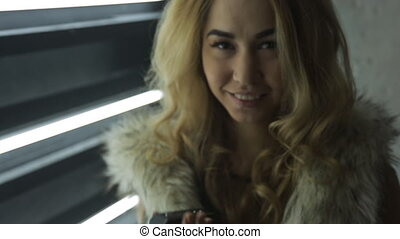 Attractive blonde woman dressed in fur jacket flirts. She...