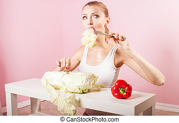 Attractive blonde woman eating vegetables.