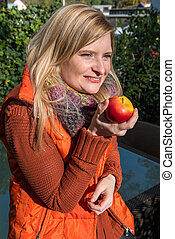 Attractive blonde woman has an apple in her hand