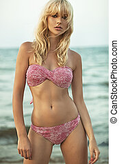 Attractive blonde woman posing at the seaside