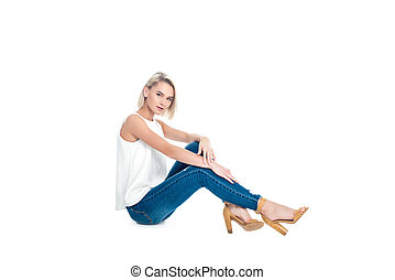 attractive blonde woman posing in jeans, isolated on white