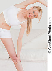 Attractive blonde woman posing while stretching in the living room in her apartment