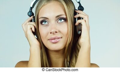 Attractive blonde woman putting on headphones and listening...
