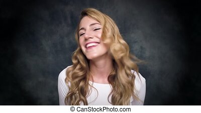 Attractive blonde woman says no and smiling on a dark...