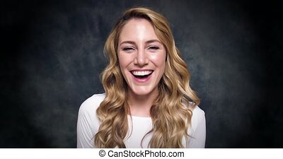 Attractive blonde woman says yes and laughs on a dark ...