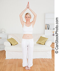 Attractive blonde woman stretching in the living room