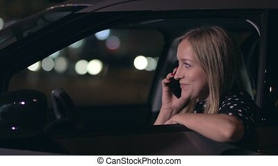 Attractive blonde woman talking on phone in car