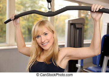 Attractive blonde woman weightlifting in a gym - Beautiful...