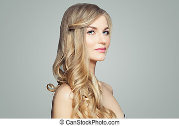 Attractive blonde woman with healthy skin and curly hair. Facial treatment, haircare and cosmetology concept