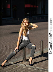 Attractive blonde woman with long hair wearing jeans and t shirt posing at the city in sun rays