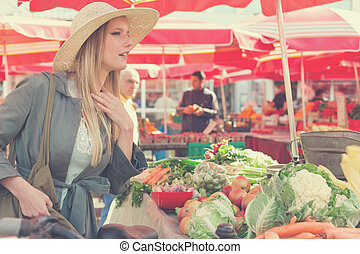 Attractive blonde woman with straw hat buying vegetables on marketplace.