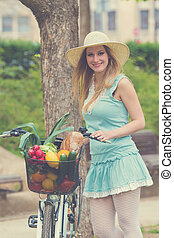 Attractive blonde woman with straw hat standing in the park and posing next to bike with basket full of groceries.