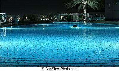 women swimming a luxury pool