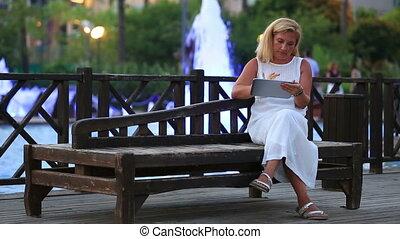 blonde women using digital tablet