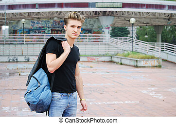Attractive blue eyed, blond young man with ruck sack...