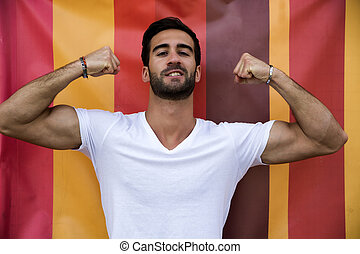 Attractive bold young man showing biceps