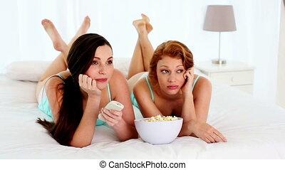 Attractive bored women watching tv - Attractive bored women...