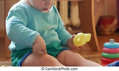 Attractive boy 2 years of playing at home with a plastic duck. The kid talks to his parents. Close-up